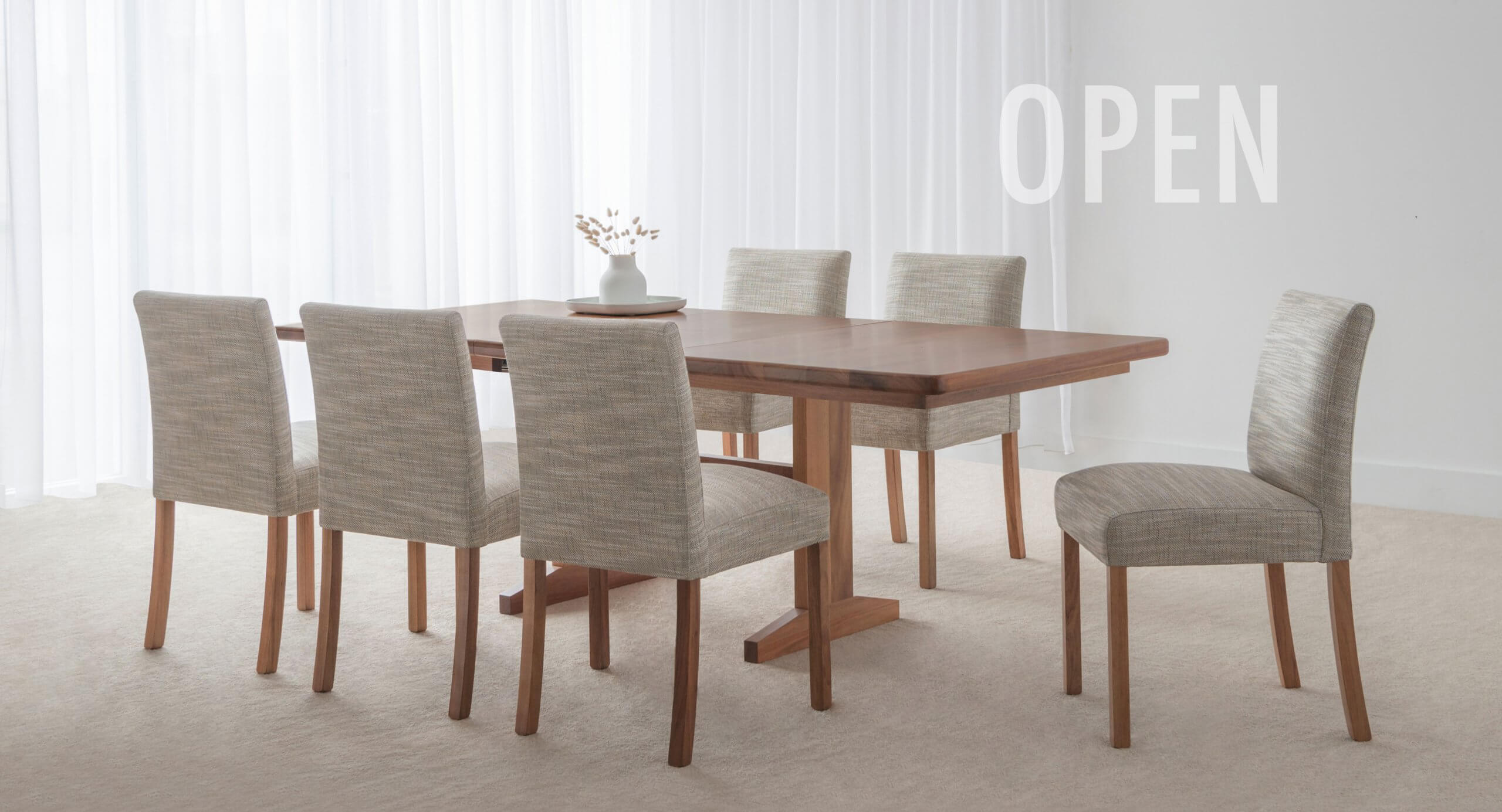 extendable dining table made in blackwood timber with upholstered fabric chairs