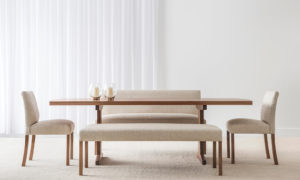 bench seat in cream fabric with matching dining chairs and blackwood table on thin pedestal leg and satin finish