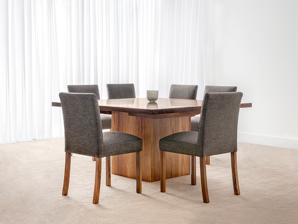 square dining table with box base and 6 grey fabric chairs in blackwood timber