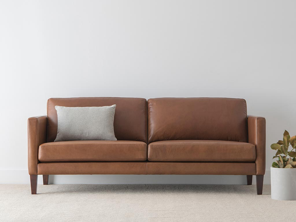 natural leather 3 seater lounge with slim arms and padded back cushions on tapered timber legs