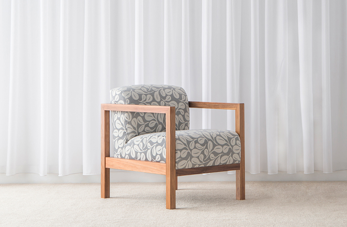 sleek armchair with square timber arms and legs and low pattern fabric seat