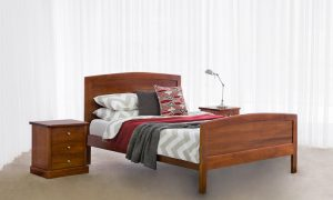 traditional chocolate timber bed with tall curved headboard and curved bed end with box bedside cabinets with 3 drawers