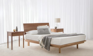 tasmanian blackwood timber bed with angled headboard and hidden legs with matching bedside tables with 1 drawer on a thin leg
