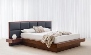 large floating bed with black leather upholstered headboard and attached floating bedside shelves in chocolate tone timber