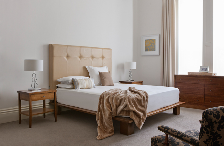fully upholstered headboard with single row deep button detailing in natural leather and floating timber base with thick square legs and slim bedside tables with 1 drawer and 1 shelf