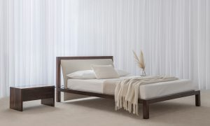 dark timber frame bed with curved upholstered headboard in soft textured fabric and solid panel dark bedside tables with deep drawer