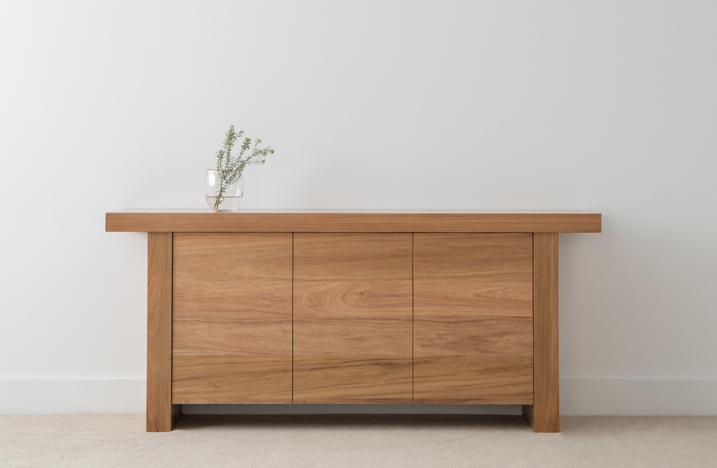 smaller sideboard in light timber with 3 push to open doors on a leg with thick top overhang