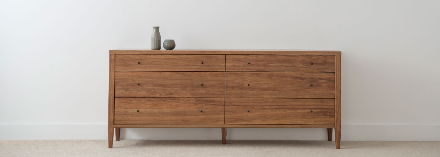 contemporary bedroom chest of 6 drawers with black handles in tasmanian blackwood timber with square edges on a slim leg