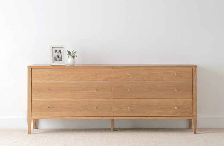 modern american oak chest of 6 drawers with 3 on each side on thin legs and small chrome handles