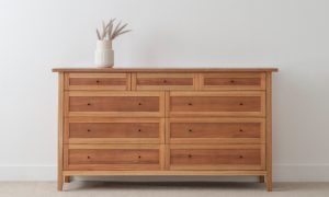 chest of 9 drawers with 3 smaller drawers and 6 larger in two tone timber and small top overhang on a leg