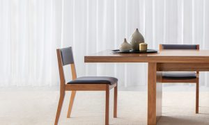 open back timber frame dining chair with angled back legs and black leather seat and back support