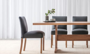 comfortable padded fully upholstered black leather dining chair with blackwood timber legs and contemporary design