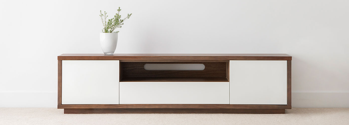 white tv cabinet on floating box base with top and side timber panels, sitting low to ground with open shelving and 3 drawers