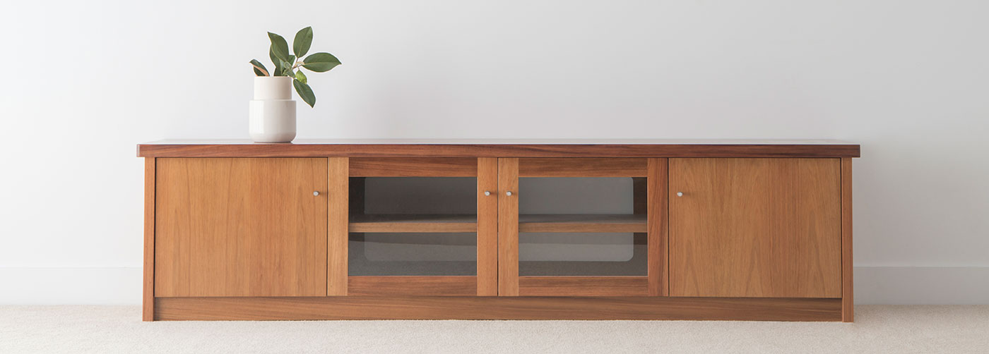 4 door tv cabinet low to ground in blackwood timber with overhang top sitting on box base with small silver handles
