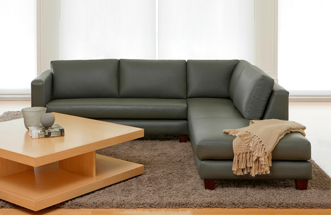 large leather modular with padded cushions and thick timber leg in dark green leather and 5 cushions