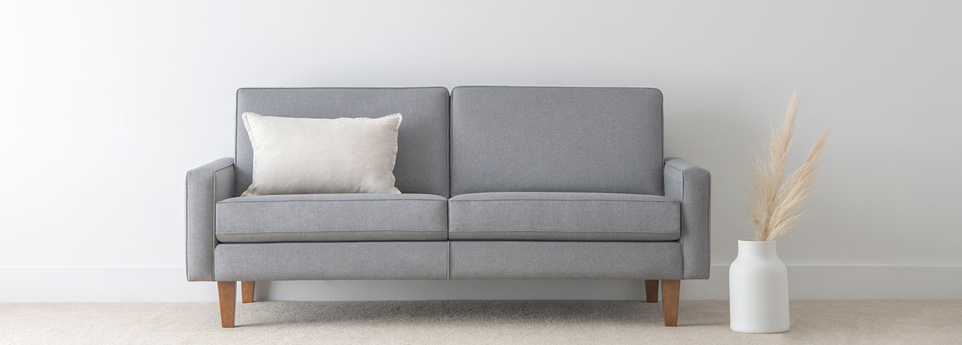 small fabric sofa with square design upholstered in light grey fabric on honey leg