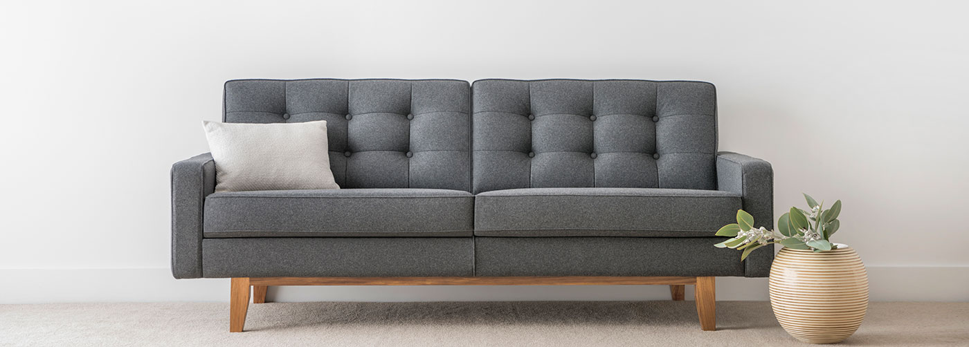 3 seater blue grey fabric sofa with button detail and low arm on timber leg