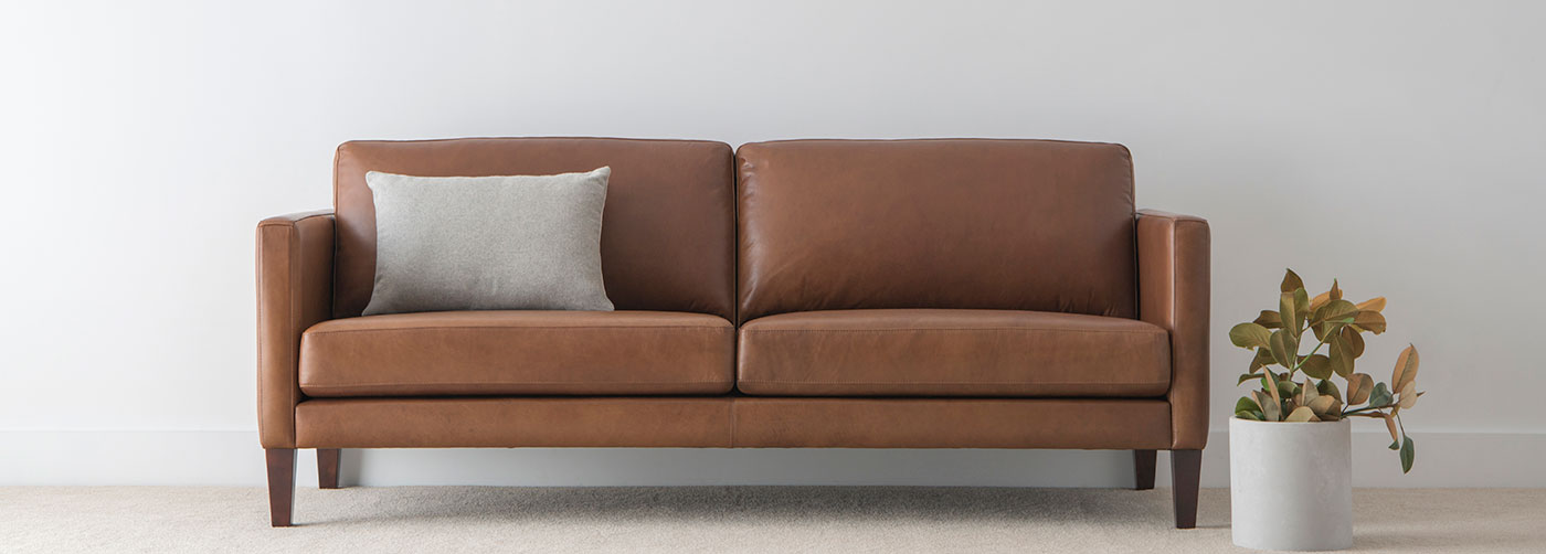 contemporary natural leather 3 seater lounge with comfortable cushions and low arm on timber leg