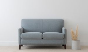 compact blue fabric sofa with narrow arms and single panel back with black timber legs