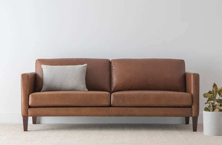contemporary natural leather lounge with padded cushions and low back on chocolate timber legs