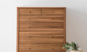 contemporary tallboy in blackwood timber with grain detailing and small black handles sitting on a leg