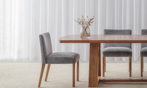 luxurious velvet dining chair with low curved back and extra wide seat sitting on blackwood timber legs