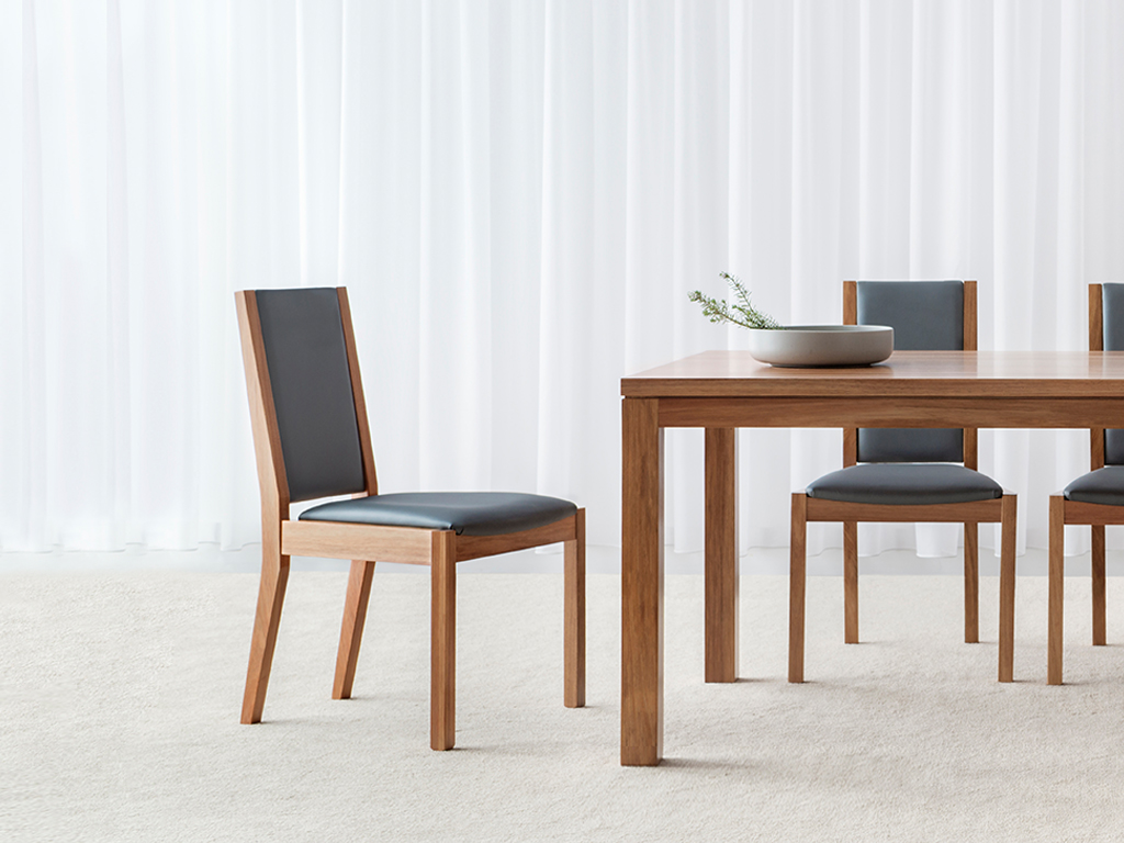 angular dining chairs with metallic blue leather seat and back support surrounded by blackwood timber frame and legs