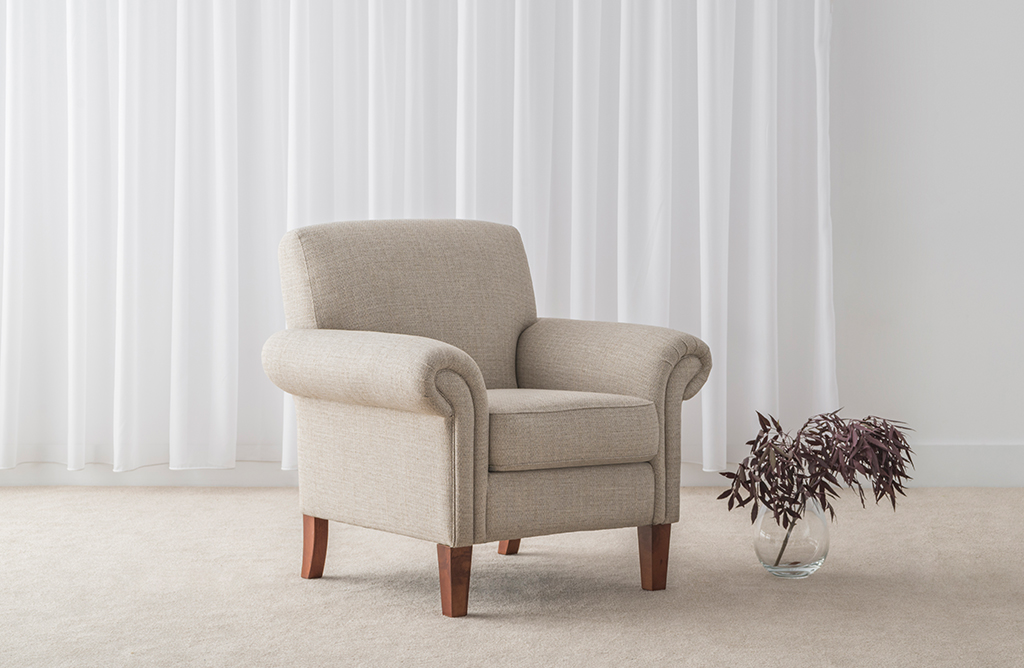 luxury hampton style armchair in soft cream fabric with elegant rolled around and padded seat on timber legs
