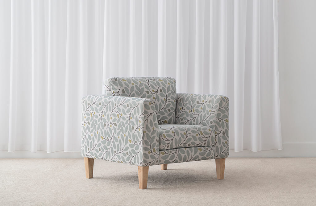 pretty floral pattern armchair with angled arm feature and low back on blonde timber leg