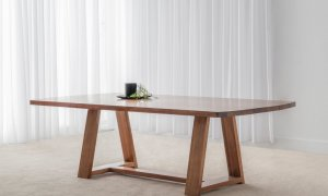 solid timber dining table with thick trestle base and rounded table ends