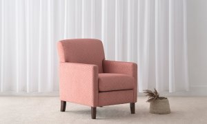 contemporary design coral fabric armchair with slim arms and supportive back on chocolate toned timber legs