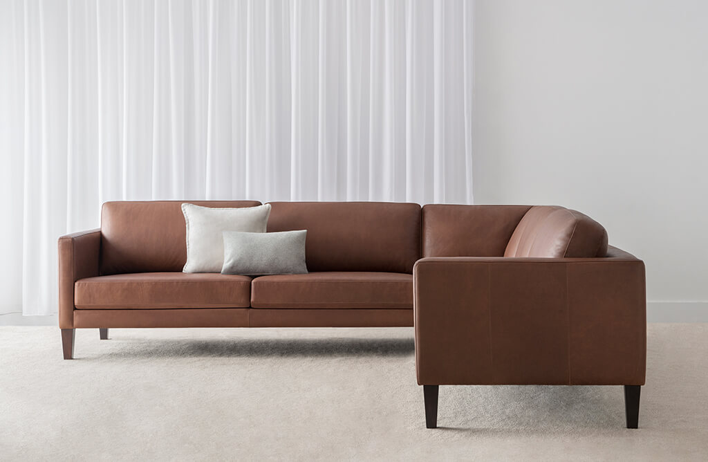 modern elegant modular lounge in natural brown leather on dark timber legs with low back cushions