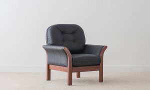 traditional armchair in black leather with rounded cushions and button detail and angled leather arms encompassed in timber frame
