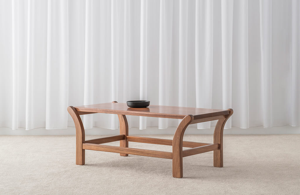 timber coffee table with bottom rail and curved legs supporting thin top