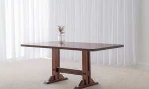 traditional dining table in toned timber with rounded corners and solid pedestal base and foot rail