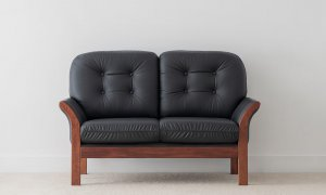 traditional lounge with rounded cushions and button detail on high timber leg upholstered in black leather with curved arm feature