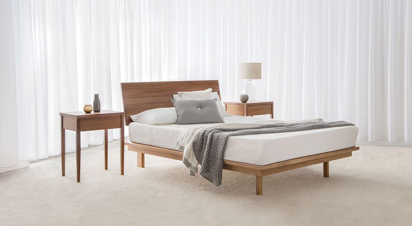 contemporary low bed frame with angled headboard and no end in blackwood timber plus matching bedside tables