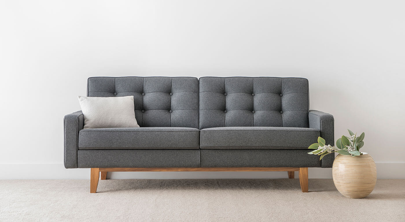 modern plush fabric 3 seater sofa with button detail and square cushions on timber base