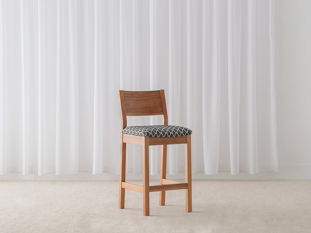 modern bar stool with geometric pattern seat and timber back support and foot rail
