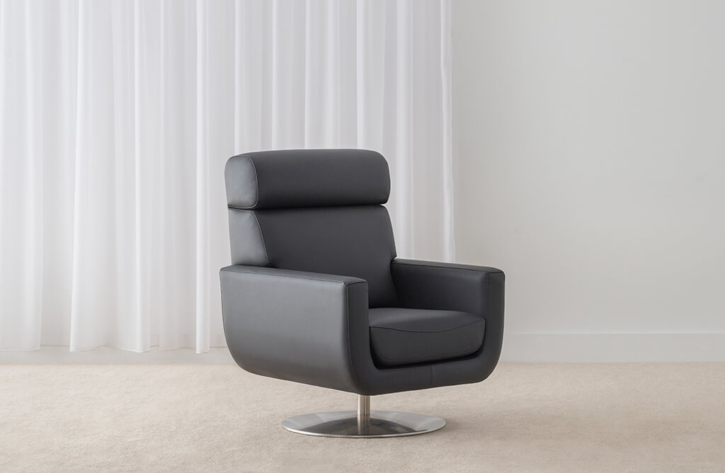 conservative high back swivel chair on chrome base upholstered in black leather with comfort headroll