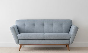modern elegant 2.5 seater lounge in textured blue fabric with pinched details and angled arms on rounded leg base