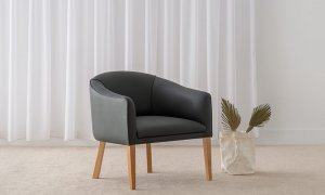 contemporary tub chair in charcoal leather with low continuous curved back and high american oak timber legs