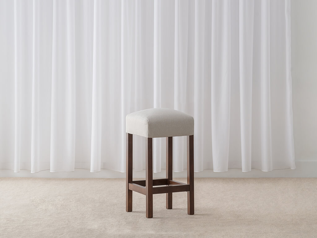 contemporary low bar stool with grey fabric seat and chocolate toned legs and foot rail
