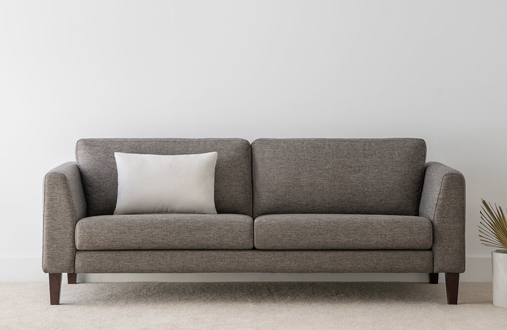 contemporary design sofa in grey fabric with angled arm feature and slim timber leg base