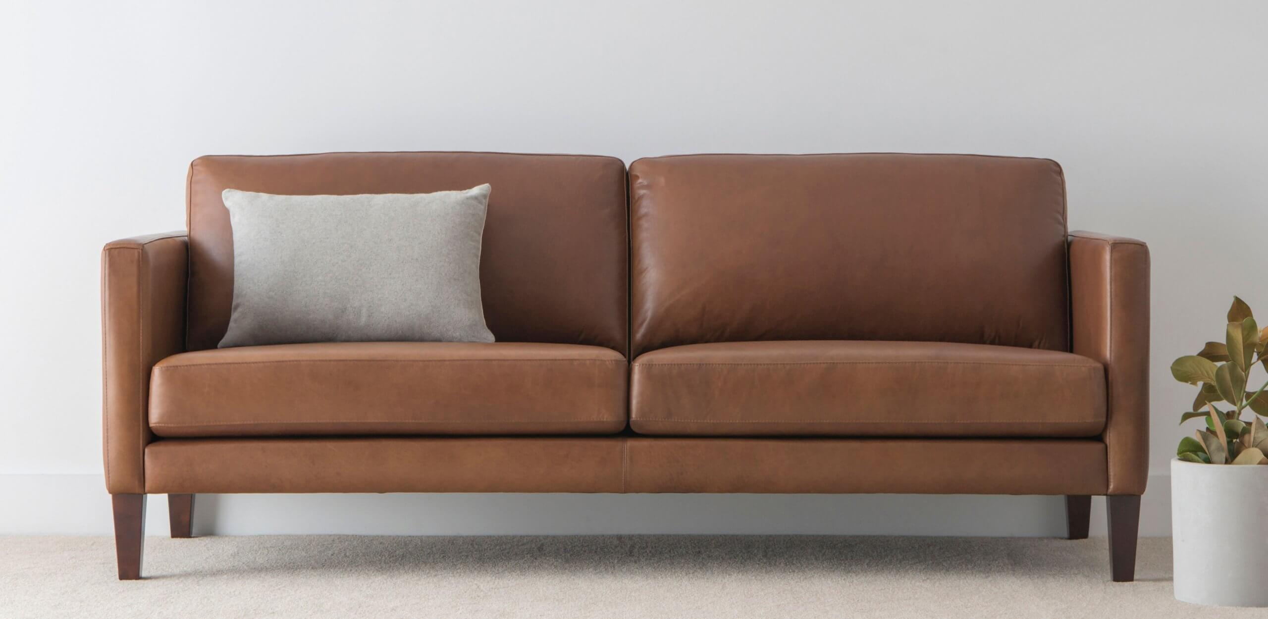 leather sofa upholstered in tan with slim arms and timber legs made in Australia