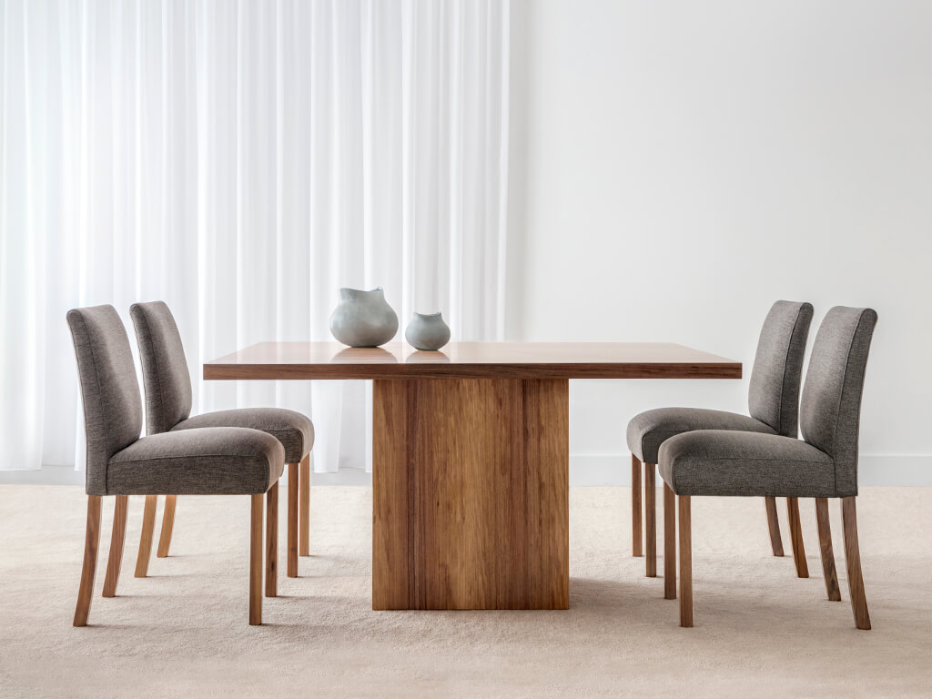 blackwood timber square dining table with matching fabric chairs in grey tones