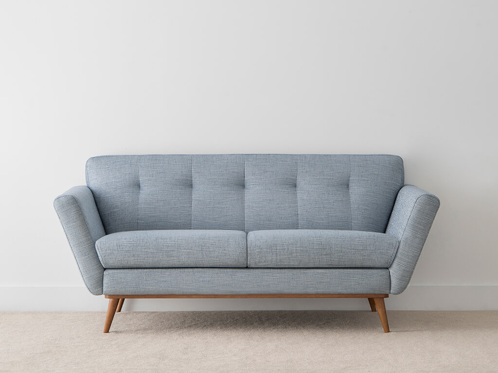 contemporary blue fabric lounge with rounded timber legs and textured blue upholstery with pinched back cushion detail