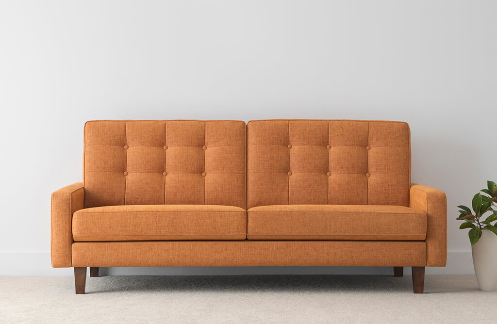 bright orange fabric sofa with button high back and timber legs