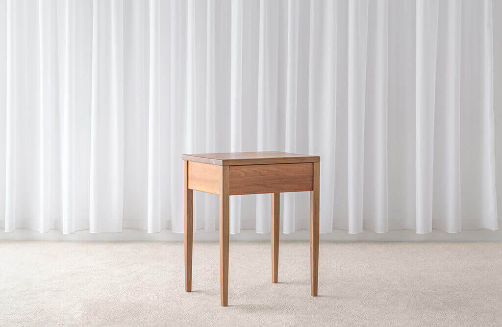 small bedside table made from blackwood timber with slim legs and single drawer