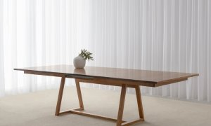 extension dining table made in blackwood timber with tapered top and open trestle base